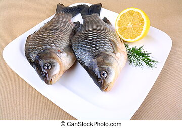 Two fresh carp on white plate with lemon