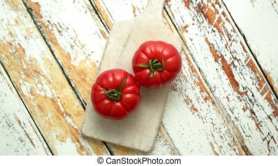 Two fresh eco tomatoes placed on white wooden cutting board...