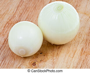 two fresh peeled onions on wooden board