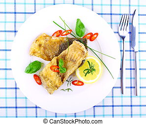Two fried fish fillets with lemon slice on white plate