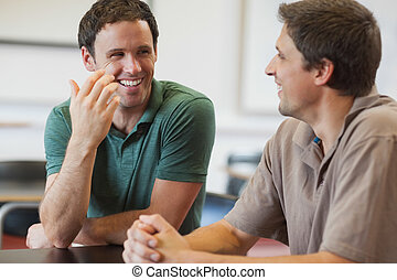 Two friendly male mature students chatting while sitting in...
