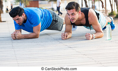 Two friends 30 years old are doing push-ups for endurance in the park near sea.