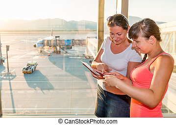 two friends are considering boarding tickets at the airport