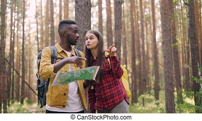 Two friends are looking at map in forest, pointing in the...