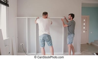 Two friends assembling the shelf, do the repairs. Man helping to his friend moving to new house.