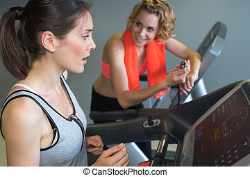 two friends at the gym exercising on the machines
