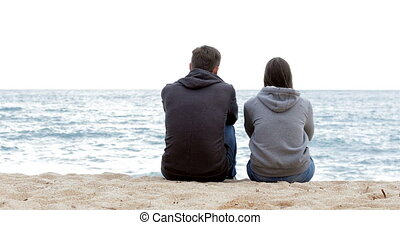 Two friends contemplating ocean on the beach - Back view of...