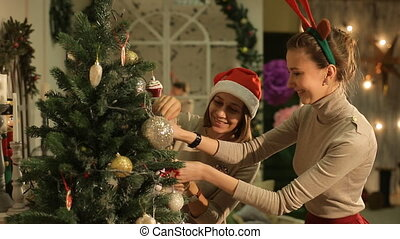 two friends decorating a Christmas tree