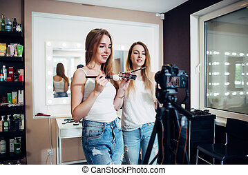 Two friends doing a makeup products review shooting a video blog standing in front of camera