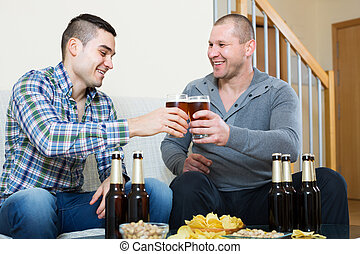 Two friends drinking beer at home