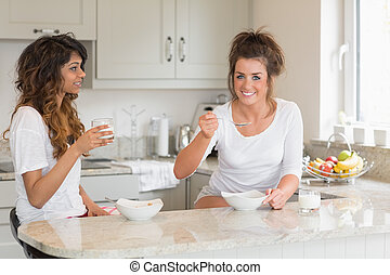 Two friends eating bowls of cereal while standing in a kitchen