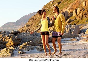 Two friends enjoying a walk on the beach