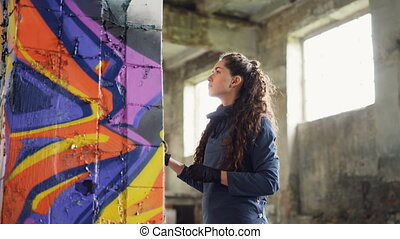 Two friends graffiti painters are drawing abstract images on...