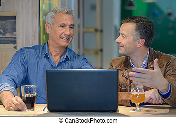 two friends having a drink and looking at the laptop