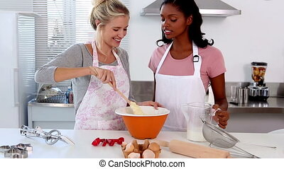 Two friends home baking together in the kitchen