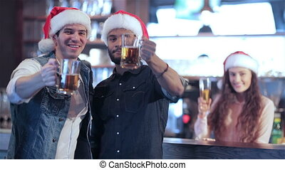 Two friends in Santa hats and the girl behind the bar is welcomed new friends