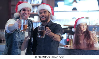 Two friends in Santa hats and the girl behind the bar with a beer raised their glasses