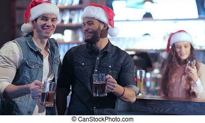 Two friends in Santa hats and the girl behind the bar with a glass of beer