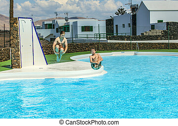 two young friends jumping in the pool