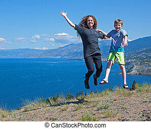 two friends jumping on hill.
