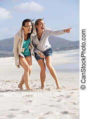 Two friends laughing and enjoying life at the beach
