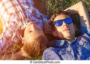 two friends lie on the grass