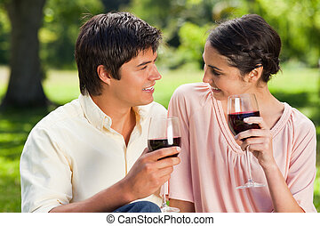 Two friends looking at each other while holding glasses of wine