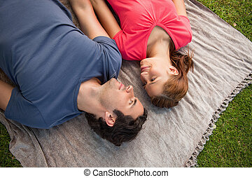 Two friends looking at each other while lying on a quilt -...