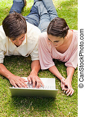 Two friends looking at something on a laptop while lying down