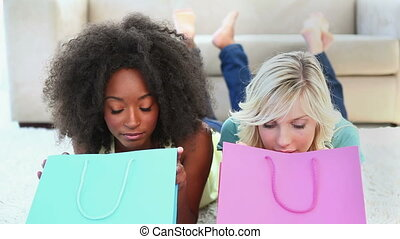 Two friends looking into shopping bags