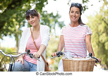 two friends on bikes in the park