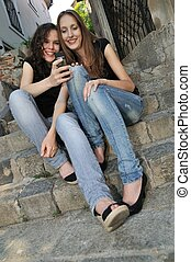 Two friends outdoors - smiling with mobile phone