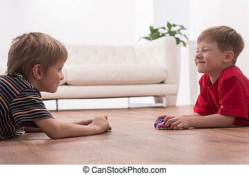 Two friends playing on floor at home. side view of boys playing with toy cars and smiling