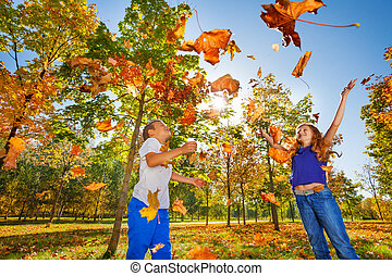 Two friends playing with thrown leaves in forest