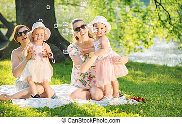 Two friends resting in the park with their daughetrs