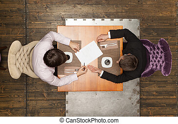 two friends sitting in cafe and eating lunch. top view of...