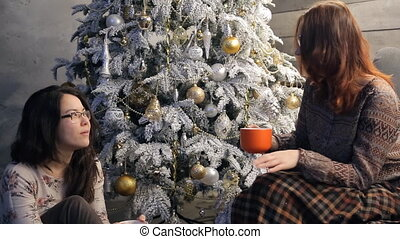 Two friends sitting talking in atmosphere of New Year holidays