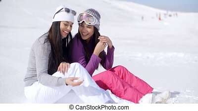 Two Friends Sitting Together on Sunny Ski Hill - Two Smiling...