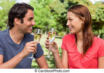 Two friends smiling as the look into each others eyes while they are holding glasses of champagne in a sunny park