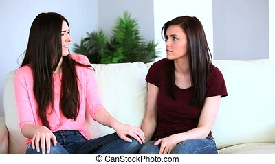Two friends speaking on the couch and receiving a text