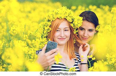 Two friends taking a selfie in a field