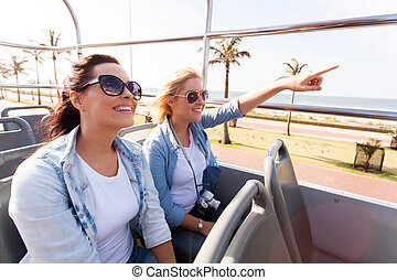 two friends taking city bus touring the town - two happy...