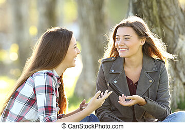 Two friends talking and laughing in a park