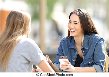 Two friends talking drinking coffee in a park