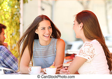 Two friends talking in a coffee shop terrace