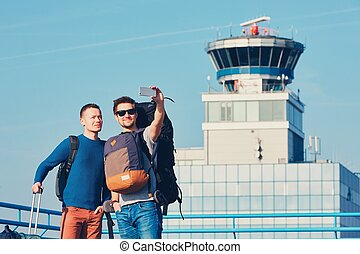 Travelers taking a selfie at the airport