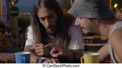 Two friends using smartwatch in street cafe