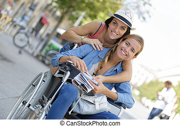 two friends visiting foreign city one sitting in wheelchair
