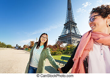 Two friends walking around Paris holding hands