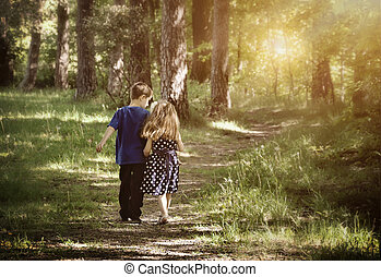 Two Friends Walking Down Path - Two young children are...